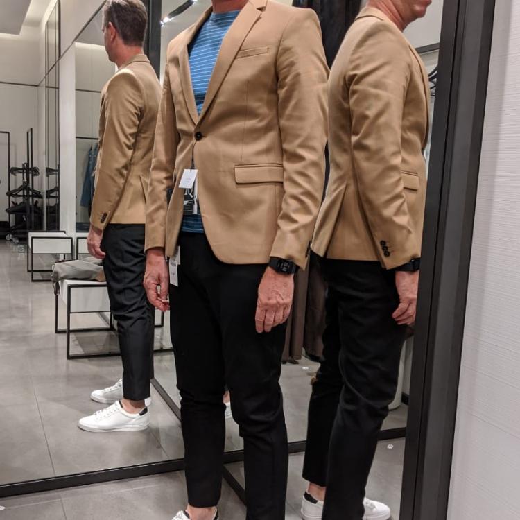 homem provando roupas na etapa de compras da consultoria de estilo para homens orientada pelo consultor Tiago Navarro
